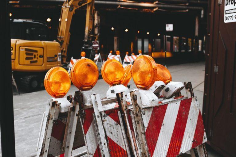 Bagger mit Baustellen Schildern im Vordergrund