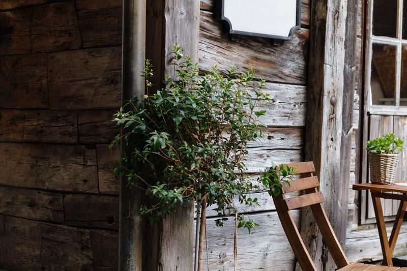 Gartenhaus aus Holz mit Blumen und Gartenstuehlen