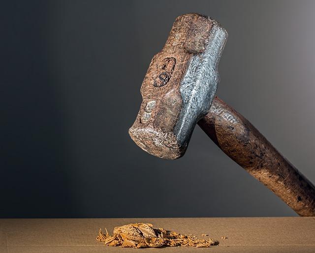 Ein Hammer schlaegt auf den Tisch